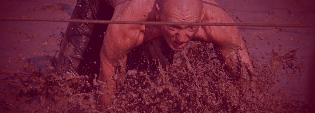 Mann konzentriert sich darauf in Matsch unter Seil hindurch zu kriechen