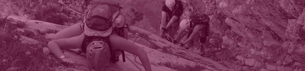 Menschen klettern an Felswand als Herausforderung